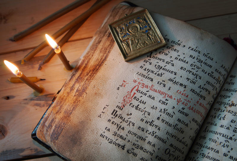 灼烧的蜡烛和老金属象在开放古老书 免版税库存图片