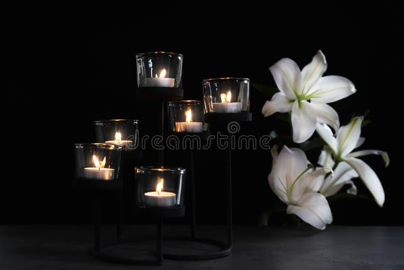 灼烧的蜡烛和花在黑暗的背景 免版税库存图片