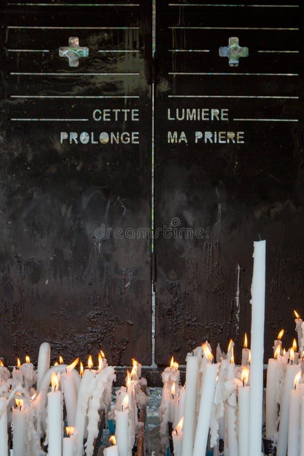 灼烧的蜡烛在一个教会里在卢尔德 免版税库存图片