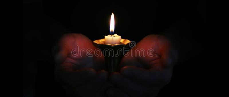 灼烧的蜡烛在手上 库存照片