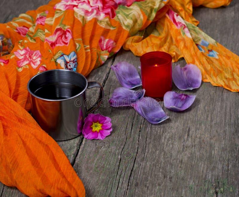 灼烧的蜡烛,钢杯子,橙色围巾 图库摄影