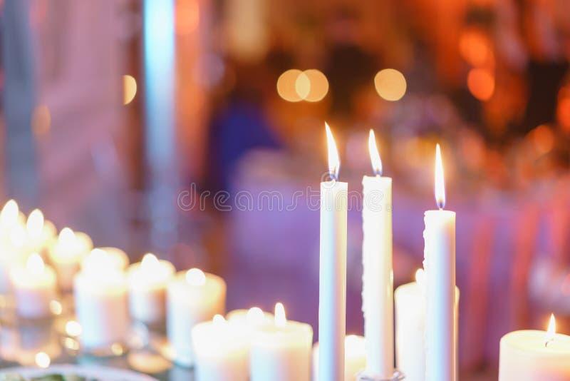 灼烧的蜡烛 在玻璃烛台的白色蜡烛在桌上站立在豪华结婚宴会在餐馆 时髦 免版税库存图片