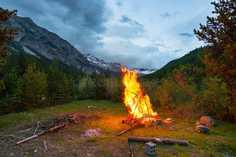 灼烧的阵营火到遥远的落叶松属里和有高处风景和剧烈的天空的杉树森林地在黄昏 夏天冒险 免版税库存照片
