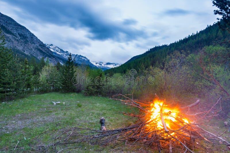 灼烧的阵营火到遥远的落叶松属里和有高处风景和剧烈的天空的杉树森林地在黄昏 夏天冒险 免版税库存图片
