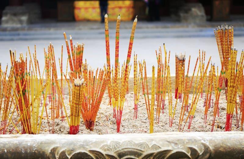 灼烧的香火在香炉,在燃烧器的中国香,烧在寺庙的香火黏附 库存图片