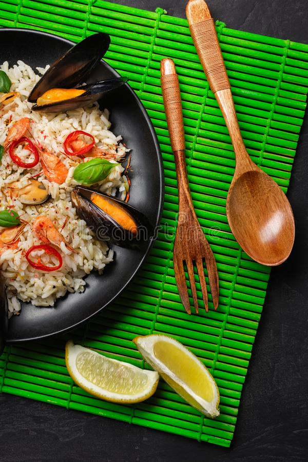 炒米用海鲜淡菜、虾、蓬蒿在一个黑色的盘子有木匙子的和叉子在绿色竹席子和石桌 库存照片