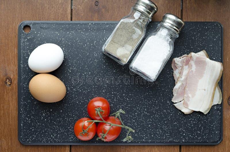炒蛋、新惯例、蛋烟肉蕃茄盐和胡椒的未加工的成份在切板顶视图 免版税图库摄影