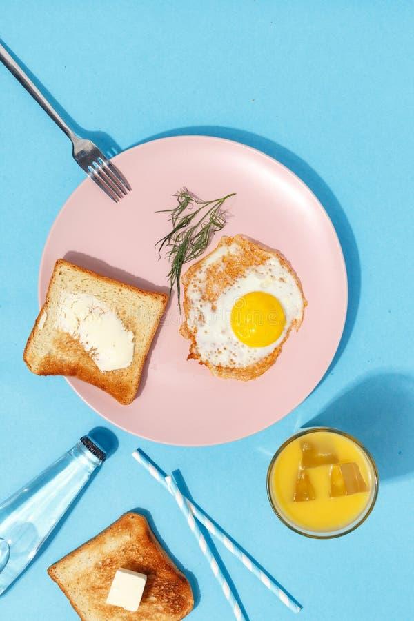炒蛋、涂奶油的多士和饮料在一张蓝色桌上 早餐顶视图 库存图片