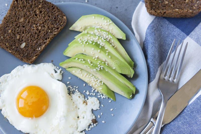 炒蛋和切好的鲕梨与芝麻,整个五谷面包在板材,健康食品片断  库存图片
