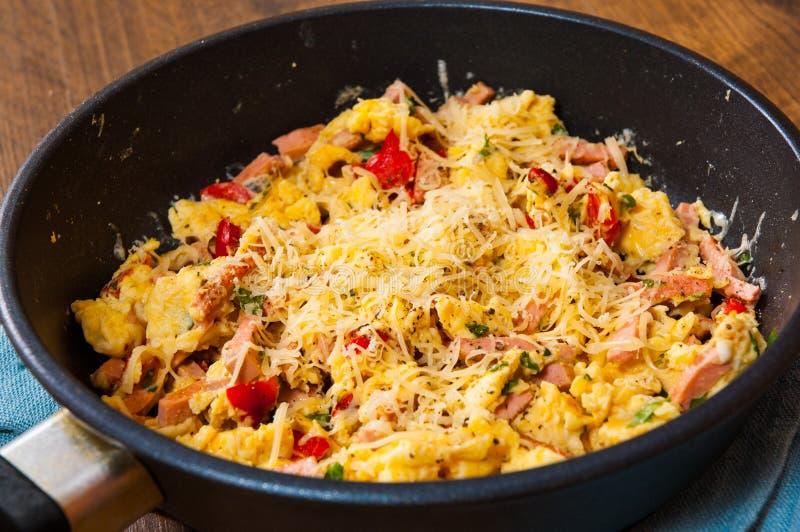 炒蛋用火腿、菜和乳酪在煎锅 免版税库存照片