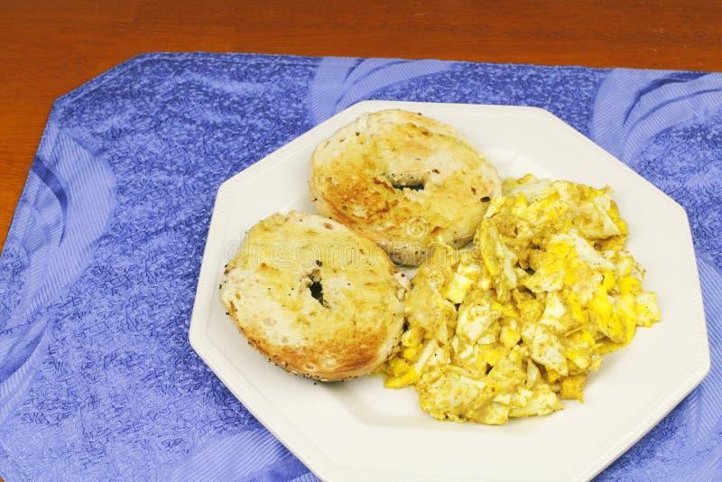 炒蛋用芥末和涂奶油的百吉卷 库存图片