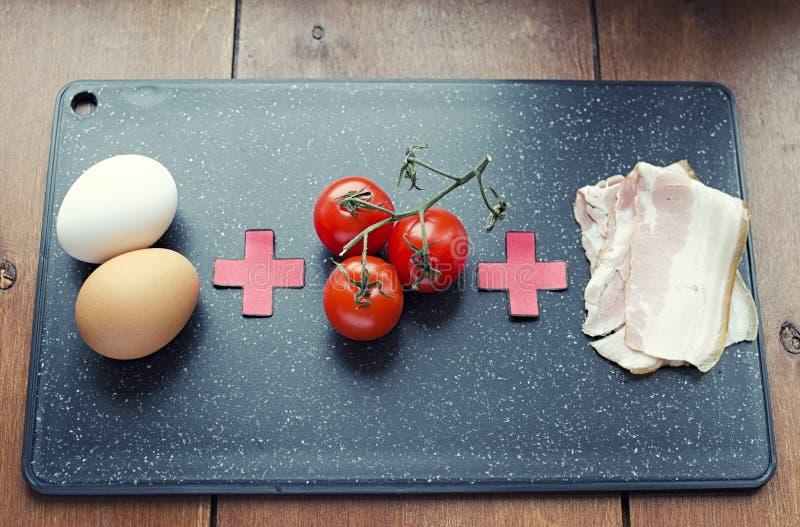 炒蛋的未加工的成份,未加工的食物惯例、蕃茄鸡蛋和烟肉在切板45景色 图库摄影