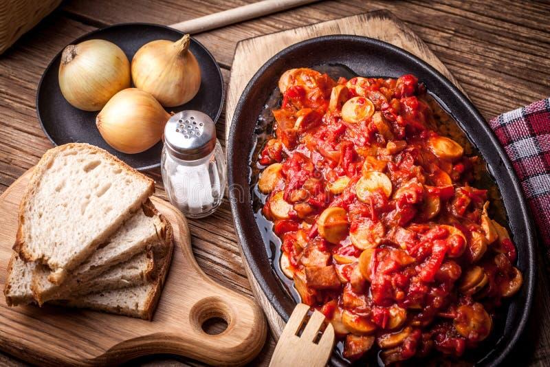炖煮的食物用胡椒、葱和香肠 库存照片