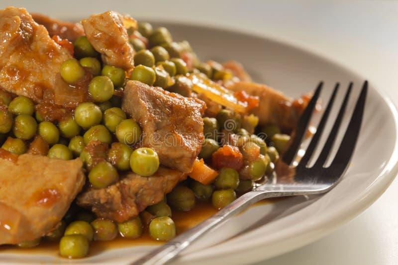 炖用豌豆、猪肉和红萝卜 免版税库存照片