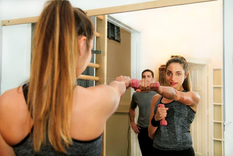 炫耀与举的重量的妇女锻炼在健身中心 库存图片