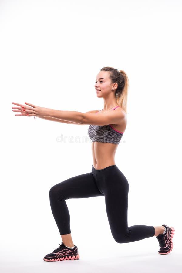 炫耀健身妇女,做矮小锻炼,在白色背景的全长画象的年轻健康女孩 库存照片