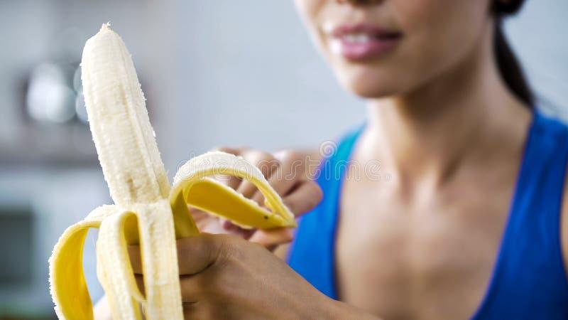 炫耀剥快餐的妇女甜香蕉,饥饿在健身房的活跃锻炼以后 库存照片
