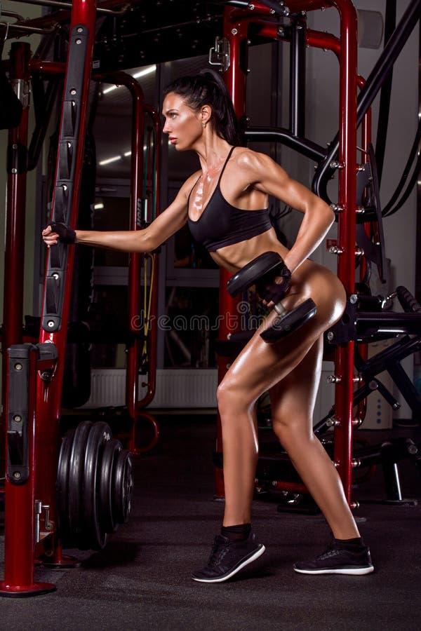 炫耀在健身房的女孩训练 免版税库存照片