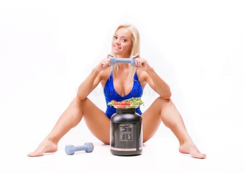 炫耀女孩用沙拉、蛋白质的一个罐头和哑铃 免版税库存照片