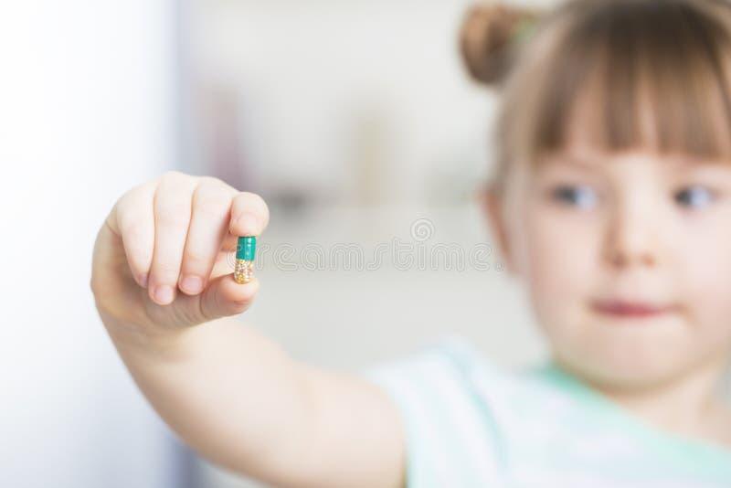 炫耀她耐咀嚼的维生素C片剂的女孩 库存照片