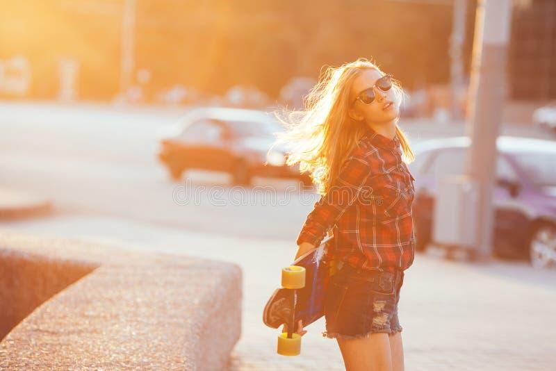 炫耀摆在与滑板的夏天的愉快的女孩 有五颜六色的longboard的时髦的幸运行家妇女在日落 免版税库存照片