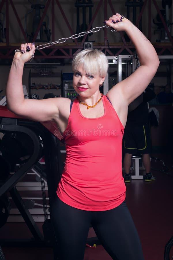 炫耀有一个链子的妇女在健身房背景 免版税库存照片