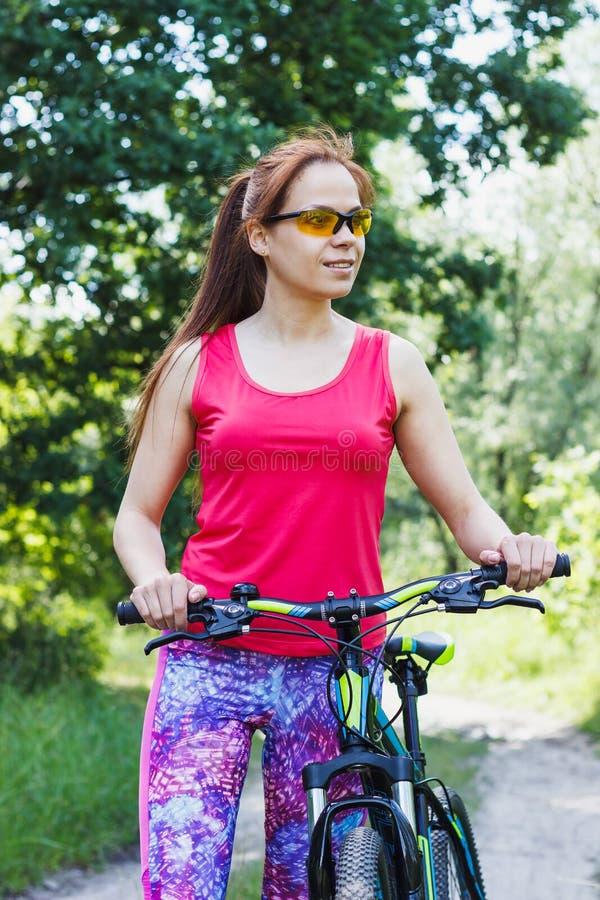 炫耀有一辆自行车的妇女在步行 免版税库存照片