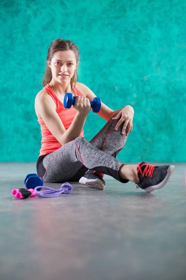炫耀有哑铃的健身女孩-在绿松石背景 甜点是不健康的 速食 节食,健康Eatin 免版税库存照片
