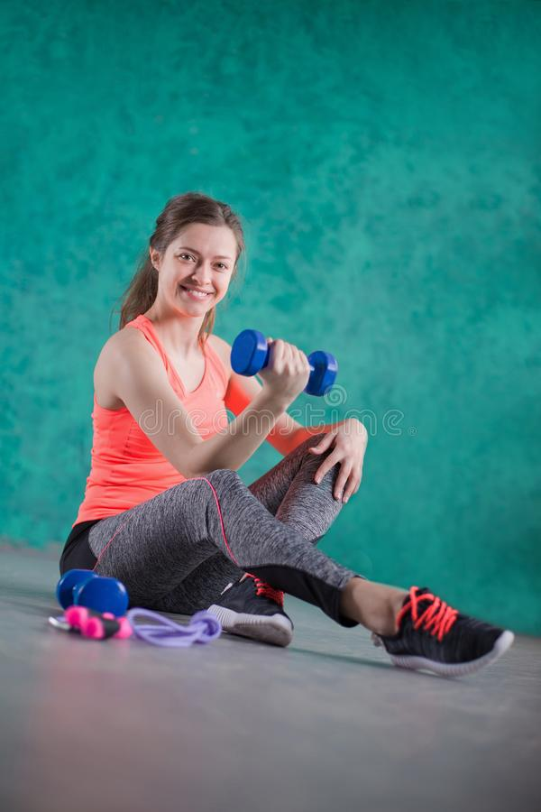 炫耀有哑铃的健身女孩-在绿松石背景 甜点是不健康的 速食 节食,健康Eatin 免版税库存图片