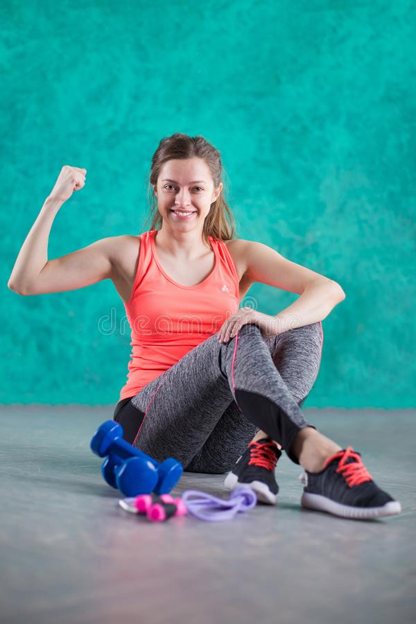 炫耀有哑铃的健身女孩-在绿松石背景 甜点是不健康的 速食 节食,健康Eatin 库存照片