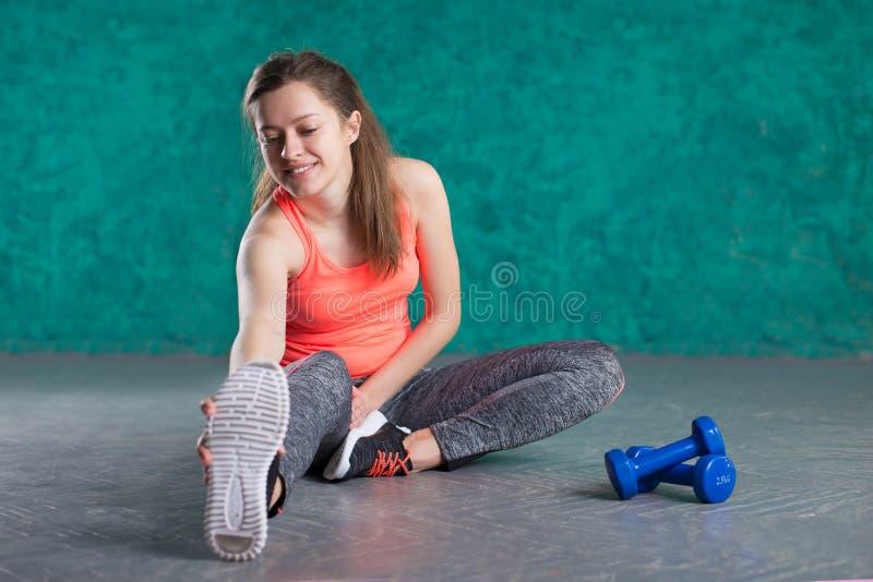 炫耀有哑铃的健身女孩-在绿松石背景 库存照片