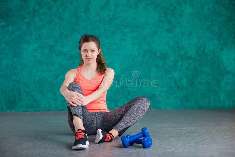 炫耀有哑铃的健身女孩-在绿松石背景 免版税库存照片