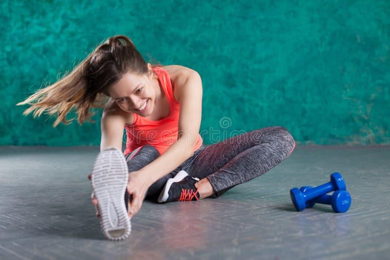 炫耀有哑铃的健身女孩-在绿松石背景 免版税图库摄影