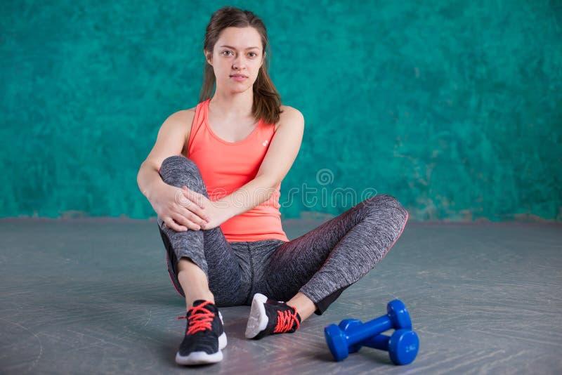 炫耀有哑铃的健身女孩-在绿松石背景 免版税库存图片