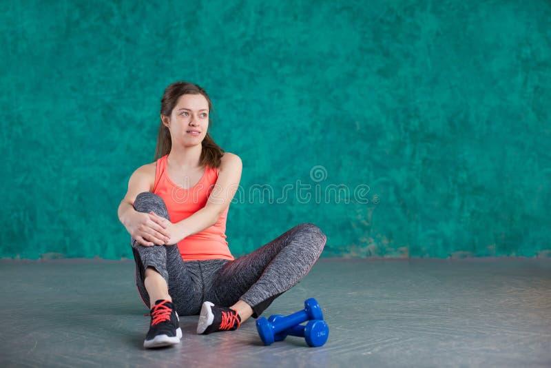 炫耀有哑铃的健身女孩-在绿松石背景 库存图片