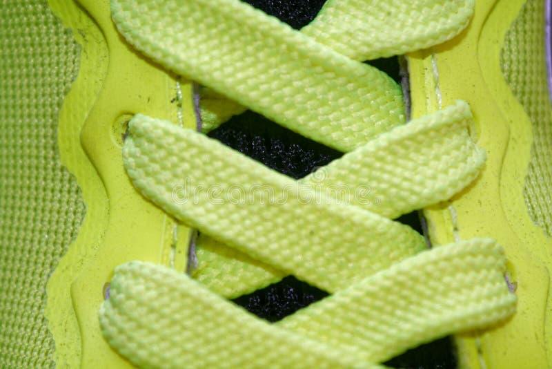 炫耀概念,鞋子接近,健康概念,在蓝色运动鞋的黄色鞋带紧密  黄色鞋子细节在跑鞋的 免版税库存照片