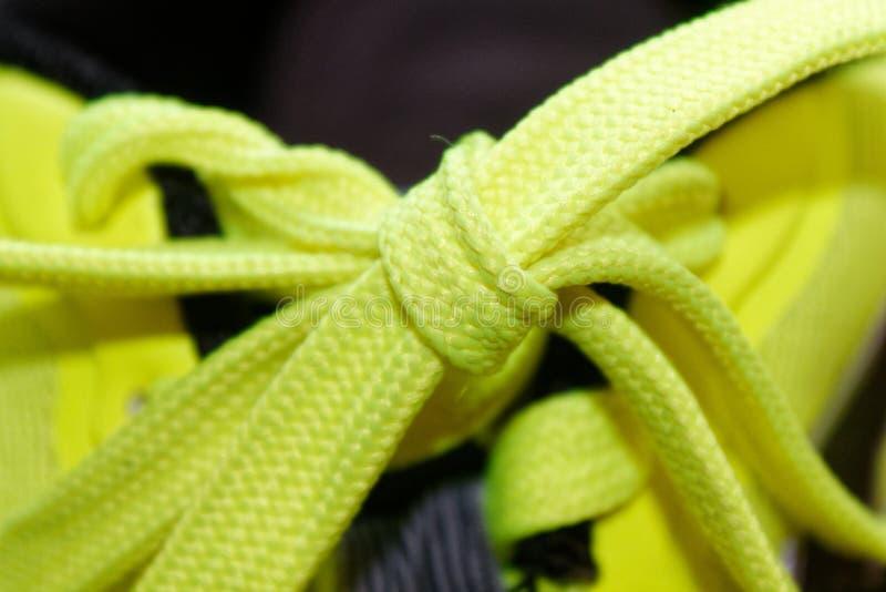 炫耀概念,鞋子接近,健康概念,在蓝色运动鞋的黄色鞋带紧密  黄色鞋子细节在跑鞋的 免版税图库摄影