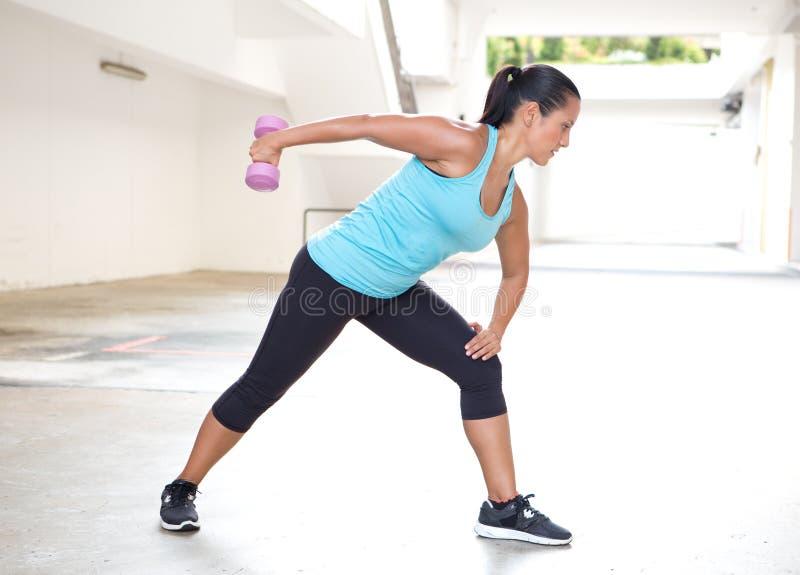 炫耀蓝色的妇女与做tricep后面引伸锻炼的哑铃 免版税库存图片