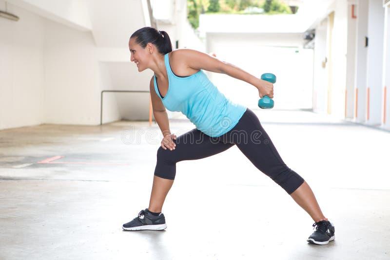 炫耀蓝色的妇女与做tricep后面引伸锻炼的哑铃 免版税库存照片