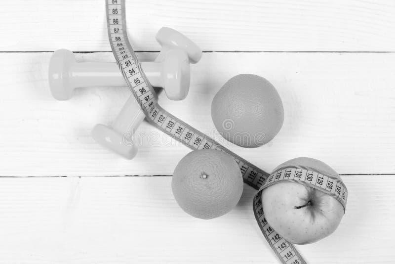 炫耀训练概念,哑铃重量用在白色葡萄酒的果子 免版税图库摄影