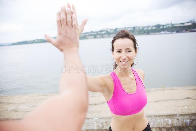 炫耀跑步在路的妇女和人外面 免版税库存图片