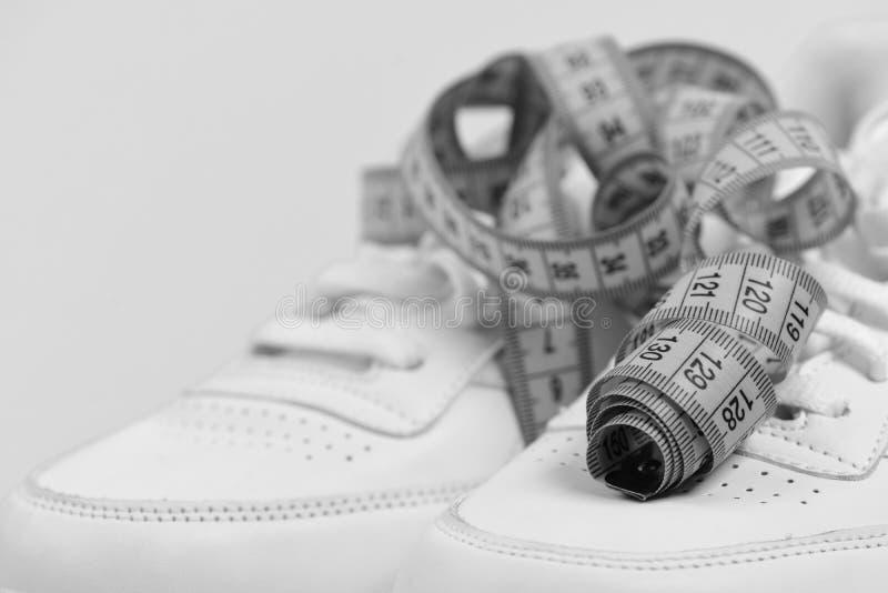 炫耀鞋子和嬉戏设备健康形状的 有测量的磁带的运动鞋在深蓝背景 库存图片