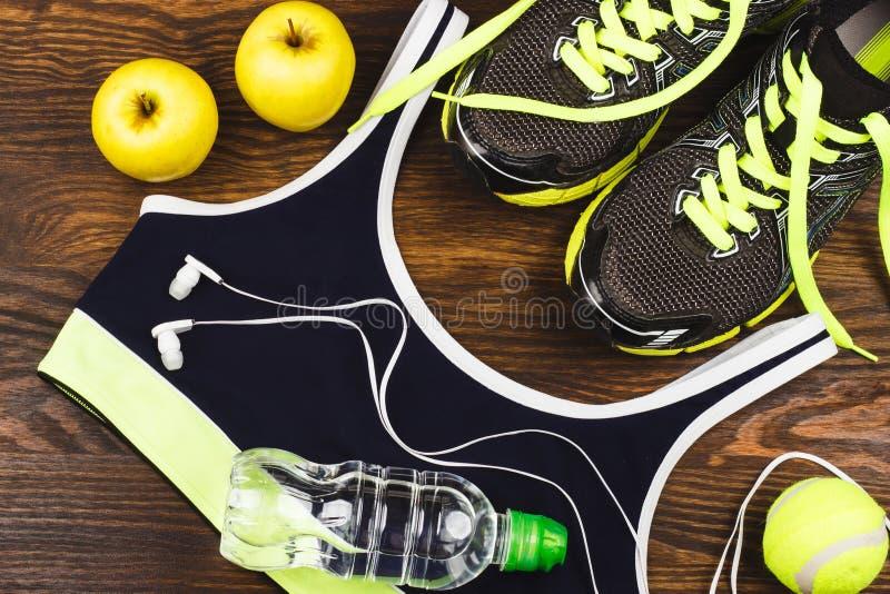炫耀项目:运动鞋、球、在木背景的瓶水和耳机 免版税库存照片
