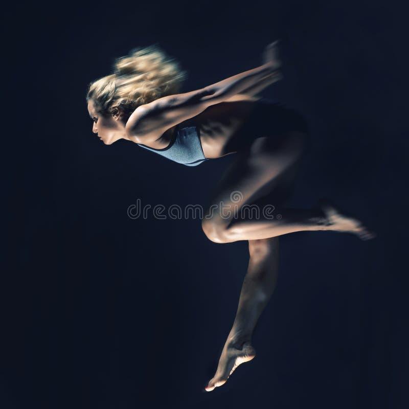 炫耀,有强健的身体的亭亭玉立的女孩做跃迁在bla 库存照片
