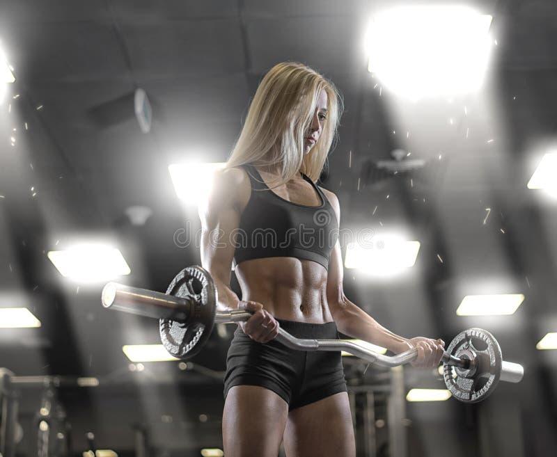 炫耀年轻性感的女孩训练在健身房 免版税库存照片