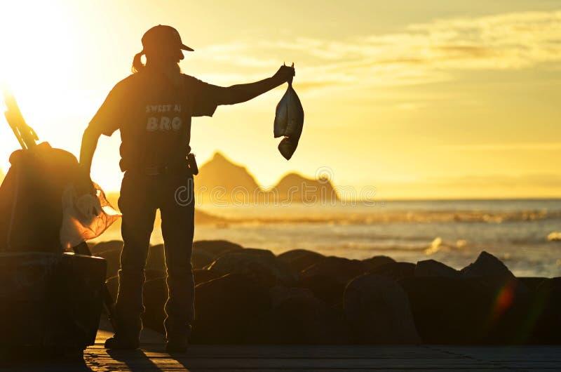 炫耀他的天的抓住的充满自豪感的地方渔夫在海滨人行道 免版税图库摄影