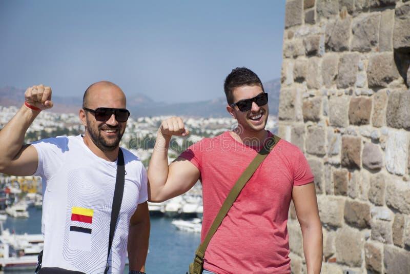 炫耀他的肌肉的两个朋友 免版税库存照片