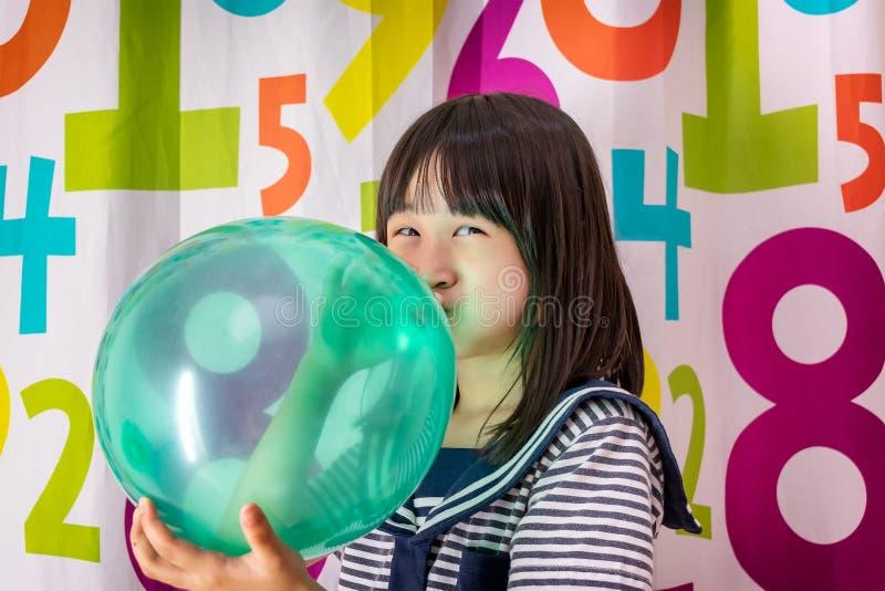 炸毁在五颜六色的背景的女孩一个气球 免版税库存照片