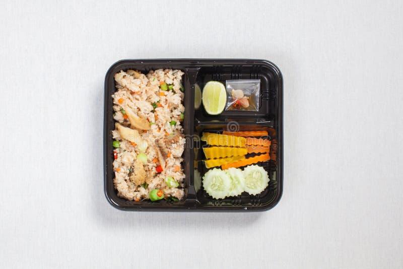 炸米饭,炸鱼放入黑塑料盒,放在白桌布上,食物盒 免版税库存图片