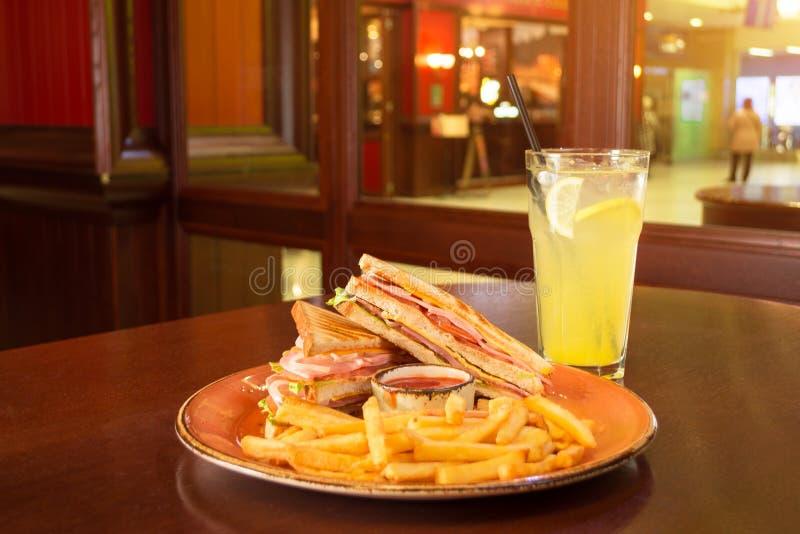 炸薯条和两个三明治与乳酪、香肠和莴苣叶子在一块难看的东西板材,在一架钢琴中间用番茄酱s 免版税库存照片
